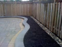Landscaping With River Rocks Along Fence Lines Allows You To Not Have To Pull Weeds River Rock Landscaping Landscaping Along Fence Fence Landscaping
