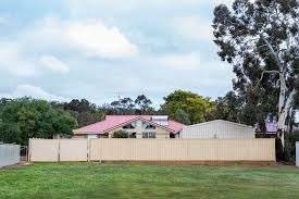 Image Of Modern House With Red Tin Roof Behind A High Fence Austockphoto