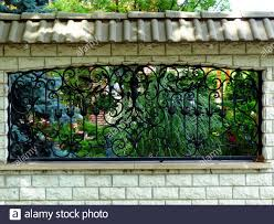 Black Wrought Iron Fence With Frame Ornate Decorative Steel Design In Textured Concrete Wall Structure Colorful Lush Foliage Mediterranean Garden Stock Photo Alamy