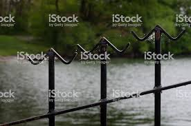 Closeup Of Three Metal Fence Finials With An Angled Crossbar Covered In Sunlit Spider Webs And Out Of Focus Watery Background Stock Photo Download Image Now Istock