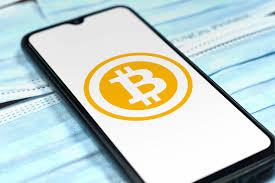 Bitcoin logo on smartphone screen over the face masks. Cov…   Flickr