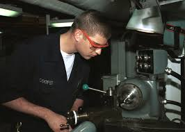 US Navy Machinery Repairman Fireman Dustin Cooper cuts a piece of a metal  fitting in the