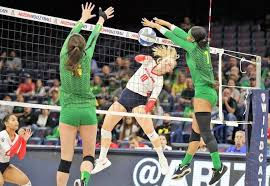 Arizona's Paige Whipple hits between the Oregon block of Abby Hansen, left,  and Ronika Stone 10-27-19 Michael Mattina Arizona Athletics |  Volleyballmag.com