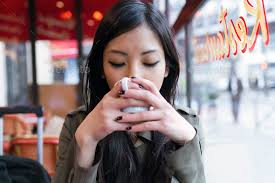 Beautiful young asian woman drinking coffee in the terrace of a ...