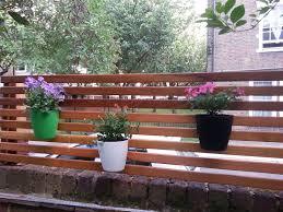 Slatted Trellis Fence With Ikea Hanging Plant Pots Hanging Plants Trellis Fence Potted Plants