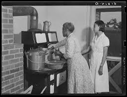 Ada Turner and Evelyn M. Driver home management and home economics  supervisor, canning English peas with pressure cooker in Mrs. Missouri  Thomas' kitchen. Flint River Farms, Georgia - intermediary roll film |