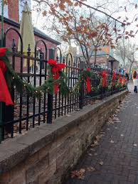 Black Wrought Iron Fence Decorated With Fresh Garland Lights Red Bows Locate Outdoor Christmas Lights Christmas Decorations Diy Outdoor Outdoor Fence Decor