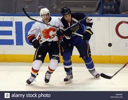 Calgary Flames Brendan Morrison (L) and St. Louis Blues Chris Stewart cross  sticks as they pursue the puck in the first period at the Scottrade Center  in St. Louis on March 1,