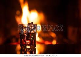 whiskey ice near fireplace stock photo