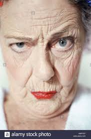 Elderly woman raising eyebrow and looking at camera, portrait Stock Photo -  Alamy