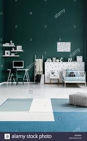Patterned Pouf On Blue Carpet In Spacious Kid S Room Interior With Green Chair At Desk With Computer Monitor Stock Photo Alamy