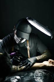 tattoo artist in black gloves drawing