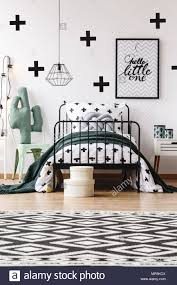 Black And White Geometric Carpet In Kids Room With Toy On Chair Next To Bed With Grey Pillow Stock Photo Alamy