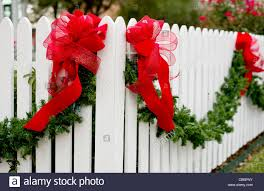 Garland And Red Bows Hang From A White Picket Fence For The Holiday Stock Photo Alamy