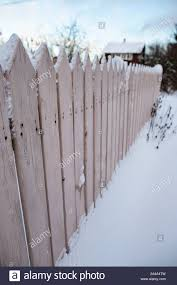 Rustic Wooden Fence Covered With Snow On A Blurred Background Of The House And Garden Winter Frosty Evening At Sunset Stock Photo Alamy
