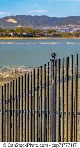 Vertical Frame Black Metal Fence With A Lake And Grassy Shore In The Background A Mountain Towering Over The Valley Under