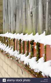 Part Of A Wooden Garden Fence And Brick Wall With Fresh Snow Stock Photo Alamy