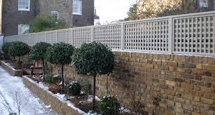 Trellis Painted Light Grey On Top Of Brick Wall Raised Bed With Standard Trees Brick Wall Gardens Brick Garden Garden Trellis Fence