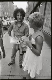 Abbie Hoffman talking to a woman on the street - Digital Commonwealth