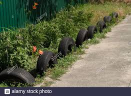 Fence Of Car Tires In Garden Stock Photo Alamy