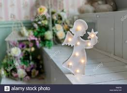 Christmas Decoration Figure Of A Little Angel With Star In Hands Isolated Angel Lamp Decor For Kids Wooden Lamp In Shape Of Angel On Flowers Interior Background Selective Focus Small Lamp For Kids Room