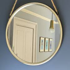 large round silver mirror on hanging rope
