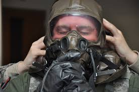 Capt. Jamie Leenman, 21st Airlift Squadron pilot, adjusts the seal on his  aircrew chemical defense equipment