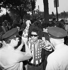 Abby Hoffman being arrested are a Vietnam protest for wearing an American  flag shirt- 1968 : OldSchoolCool