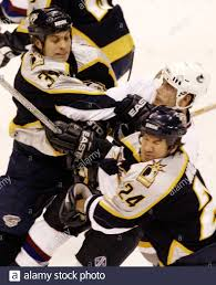 Vancouver Canucks' Brendan Morrison (C) is hit by Nashville Predators' Cale  Hulse (32) and Scott Walker (24) during their NHL game in Vancouver,  British Columbia, March 20, 2003. REUTERS/Lyle Stafford LS Stock Photo -  Alamy