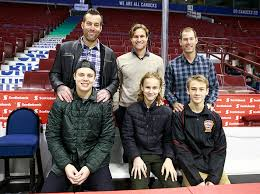 Former Vancouver Canuck players (L-R), Todd Bertuzzi, Markus Naslund and Brendan  Morrison stand behind their sons Tag Bertuzzi, Alex Naslund and Brayden  Morrison on the Canucks bench before the NHL game between