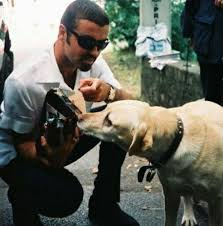 George Michael's pining dog sniffs flowers left for tragic owner as she's  comforted by mourning fans - Mirror Online