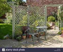 Small Domestic Garden Patio With Metal Table And Chairs Natural Stone Slabs And Painted Trellis Stock Photo Alamy