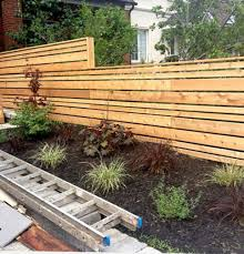 The Staggered Widths In This Modern Horizontal Fence Break Up The Height In A Nice Way I Also Like The Cap De Wood Fence Design Fence Landscaping Fence Design