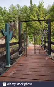 Brown And Turquoise Painted Wooden Footbridge And Wrought Iron Metal Fence Gate Leading To A Private Front Yard Country Garden In Summer Stock Photo Alamy