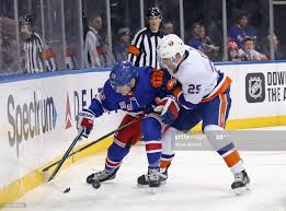 Devon Toews of the New York Islanders holds off Adam Fox of the New... News  Photo - Getty Images