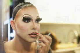 young man applying drag makeup stock