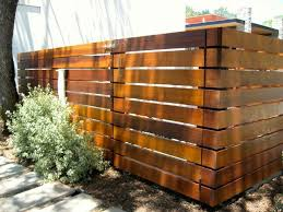 Dark Stained Wood Privacy Fence With Horizontal 2x6 Slats And Thick 4x4 Posts Gaps Appear To Be 1 Inch Between Slats Backyard Fences Fence Design Fence Styles