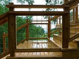 Hog Wire Fence Panel Installed In Wooden For Staircase Railing Through It We Can See The Green Trees In 2020 Deck Railing Design Wire Deck Railing Building A Deck