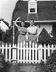 A Young Couple Smiling And Waving From Behind The White Picket Fence Cape Cod Style House Cape Cod House Exterior Cape Style Homes