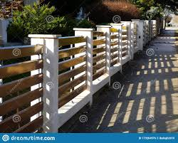 White Stucco Finished Fence Piers With Horizontal Brown Metal Slats Stock Photo Image Of Plant Modern 173264976