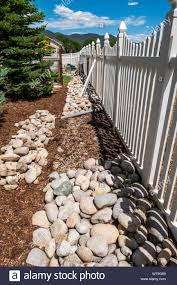 River Rocks Over Weed Landscape Barrier Used To Create A Garden Border Stock Photo Alamy