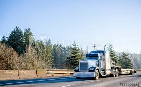 Powerful Bonnet American Idol Big Rig Semi Truck With Step Down Semi Trailer Moving On Wide Highway With Safety Fence Buy This Stock Photo And Explore Similar Images At Adobe Stock
