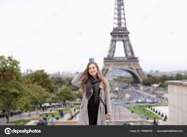 grey coat standing with eiffel tower