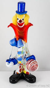 the murano glass clown stands holding a
