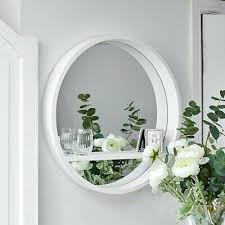 white round mirror with shelf wall