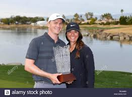 La Quinta, California, USA. January 20, 2019 Adam Long and wife Emily poses  with the winner's trophy after the final round of the Desert Classic golf  tournament on the Stadium Course at