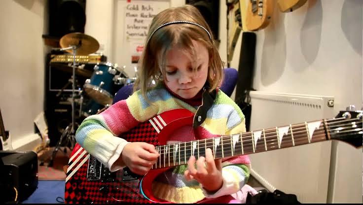 niña toando guitarra