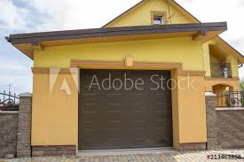 View From The Clean Paved Street Of Detached Garage With Big Automatic Door New Residential Cottage With Balcony Behind Brown Brick Forged Fence Real Estate Property And Prosperity Concept Buy This
