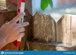 Woman S Hand Holding Small Level To Check Fence Post In Back Yard Stock Photo Image Of Contractor Building 167014966