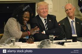 President Donald Trump (C) draws laughs from Fontana, California Mayor Acquanetta  Warren (L) and Florida Gov.